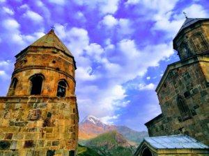 虹色に染まる山と教会