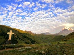 十字架と夕陽にくれる山