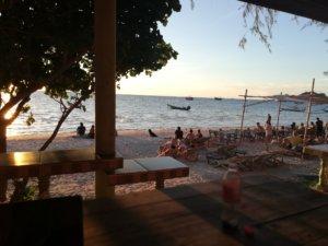 ビーチで夕日を眺める人々