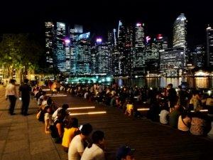 シンガポールで階段に座り夜景を見る人々