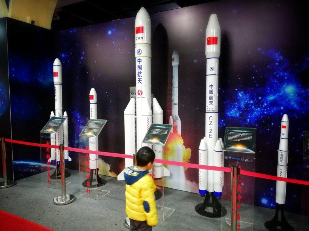 展示された中国ロケットを眺める少年,A boy looking at the Chinese rocket on display