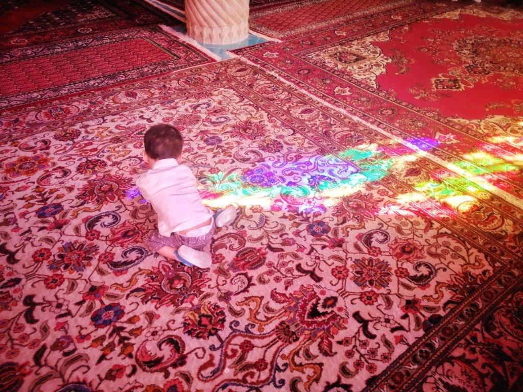 イランのピンクモスクで光と遊ぶ少年,Boy playing with light in pink mosque in iran