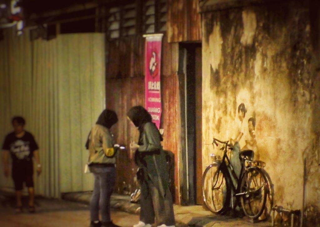 トリックアートの前で記念撮影をするヒジャブの女性