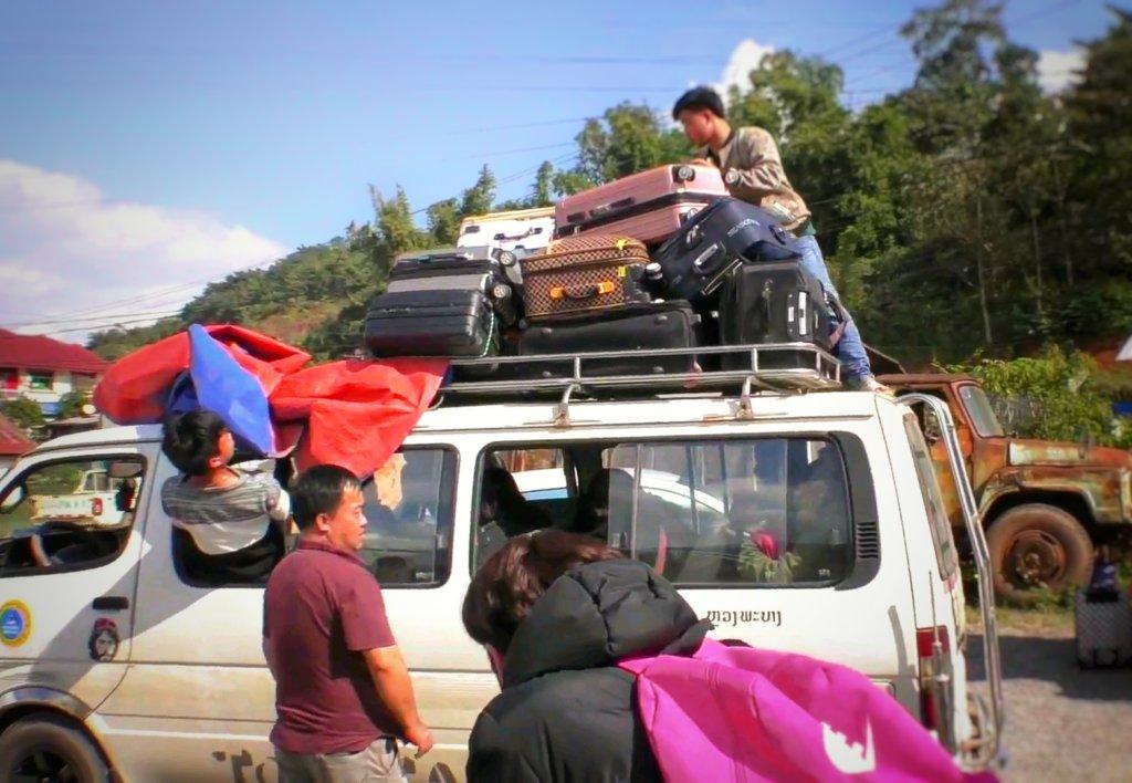 ラオスの国境を越えるトランクを山ほど積んだバス,Buses with piles of trunks crossing the border of Laos