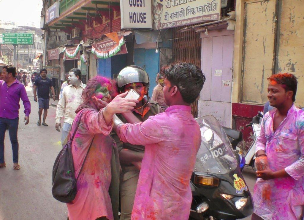 インドのホーリー祭りでカラフルに染まりながらも自撮りをしている女性