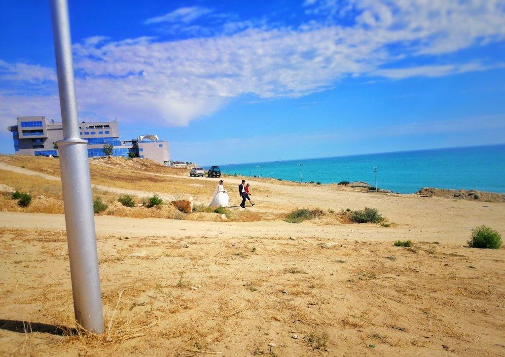 アクタウ:浜辺を歩く新老夫婦
